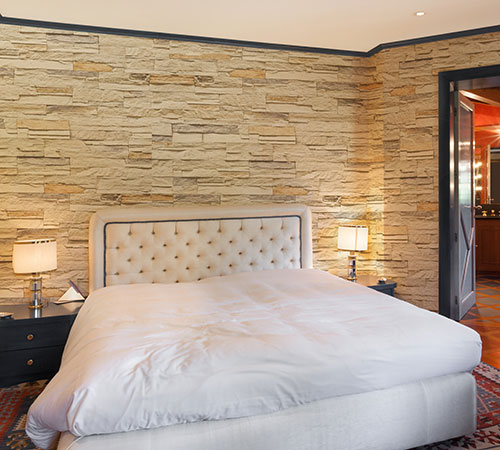 Bedroom decorated in the interior with Mathios Stone Sierra Cream, architectural stone veneer.