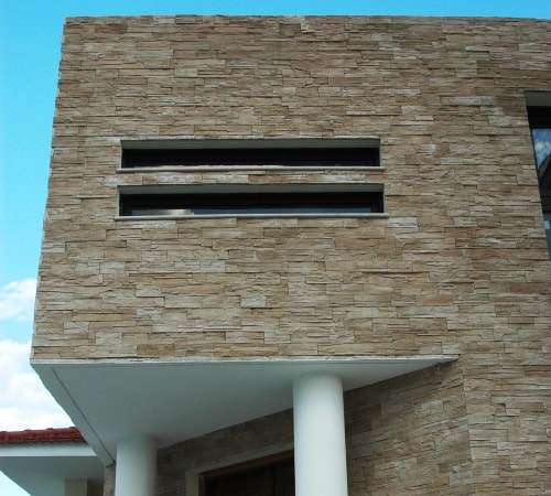 Outdoor texture display of Mathios Stone Sierra Gold. An architectural stone veneer that blends nicely with this modern home.