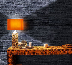 A modern wooden table and a reading lamb. On the wall, Mathios Stone Dune Eclipse stone veneer is applied.